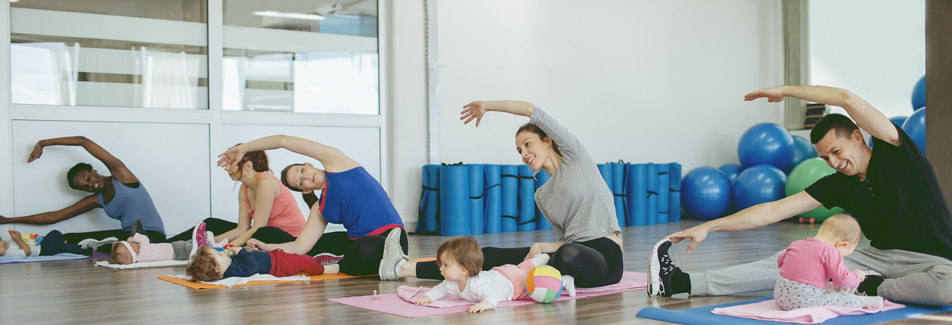 Parents doing yoga in a gymnasium with their babies.